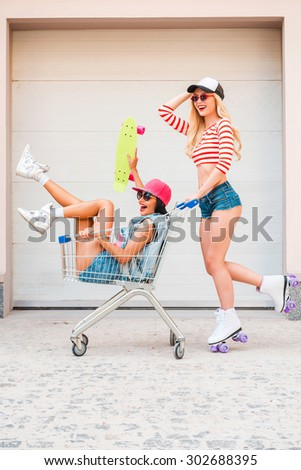 They always have fun together.  Side view of cheerful young woman on roller skates carrying her female friend in shopping cart and smiling while skating against the garage door - stock photo