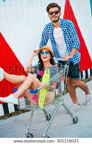 They always have fun together. Top view of joyful young woman sitting in shopping cart while her boyfriend pushing it - stock photo