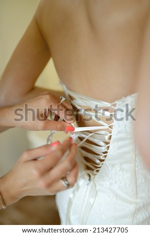 They are stringing the bride dress