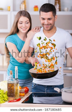 They love cooking together. Beautiful young couple cooking together in the kitchen - stock photo