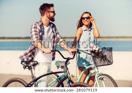They love the active life. Happy young couple rolling their bicycles and looking at each other with smileswhile walking outdoors - stock photo