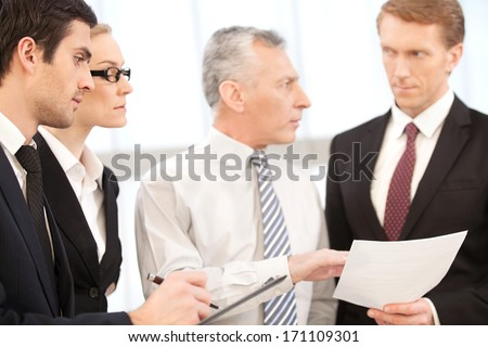 They need an advice of professional. Four business people discussing something and holding documents in their hands