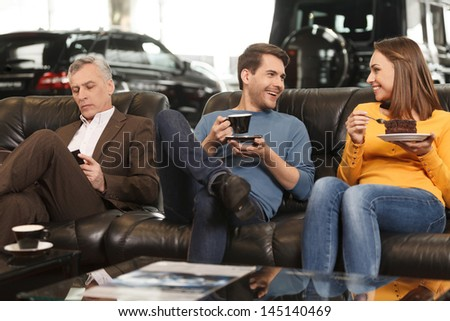They need some break to make a right choise. Three car dealership customers having a break before making final decision about car they want - stock photo
