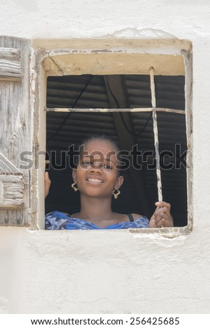 THIAROYE, SENEGAL, AFRICA, JULY 18, 2014, Unidentified woman standing by the window of her house  - stock photo