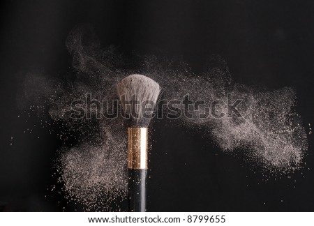 thick black brush and loose powder particles scattered around - stock photo