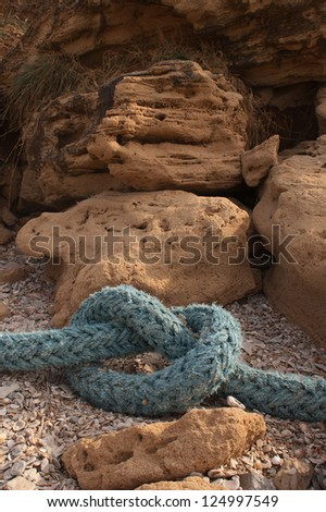 Thick blue rope with a simple knot on a rocky river bed. - stock photo