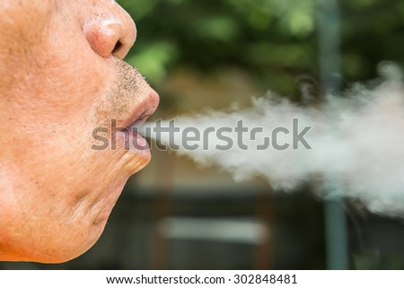 Thick cigarette smoke comes out of the mouth of the smoker old man. - stock photo