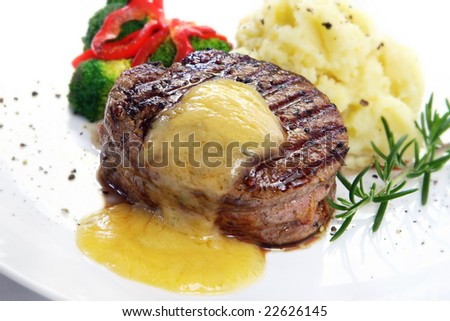 Thick-cut beef filet steak with Bearnaise sauce, served with mashed potatoes, broccoli and red bell peppers. - stock photo
