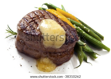 Thick-cut fillet steak with Bearnaise sauce, accompanied by green beans and yellow capsicum. - stock photo