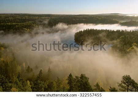 Thick fog covering the forest and the lake in early morning landscape. Peaceful view from the Aulanko lookout tower in Finland. - stock photo