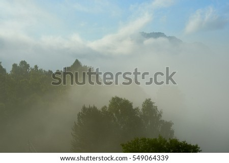 Thick fog on the shore of a mountain lake