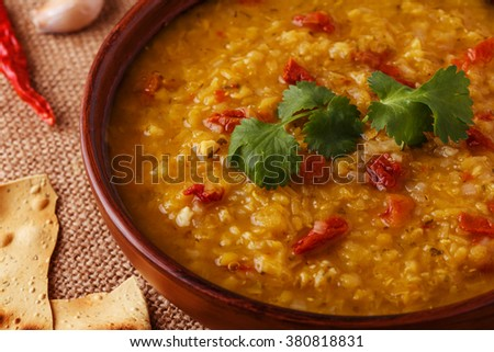 Thick indian red lentil soup with cilantro served with indian flat bread on a wooden background. - stock photo