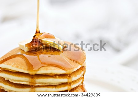 Thick maple syrup pouring onto a stack of fresh pancakes. Shallow depth of field with selective focus on butter. - stock photo