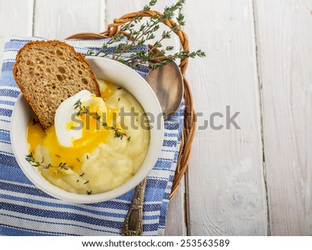 Thick mashed potatoes with poached egg and a slice of bread with thyme. selective Focus - stock photo