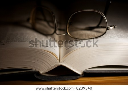 Thick open book in the dark with glasses on it