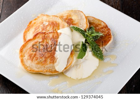 thick pancake with sour cream and syrup - stock photo