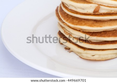 Thick pancakes are stacked on a plate