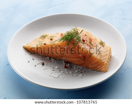 Thick piece of raw salmon with dill and pink peppercorns - stock photo