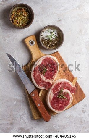 Thick raw beef roll with seasoning and rosemary, selective focus - stock photo