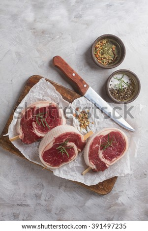 Thick raw beef with seasoning and rosemary, selective focus - stock photo