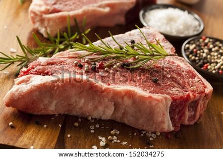 Thick Raw T-Bone Steak with Seasoning and Rosemary - stock photo