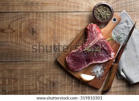 Thick raw T-bone steak with seasoning and rosemary, selective focus