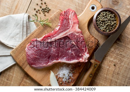 Thick raw T-bone steak with seasoning and rosemary, selective focus - stock photo