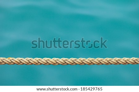 Thick ship rope on the background of sea water. Linen sailboat cord for big yacht closeup - stock photo