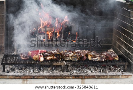 Thick slices of meat from chianina cow grilling over the embers - stock photo