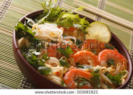 Thick soup with shrimps, noodles and herbs close up in a bowl on the table. horizontal