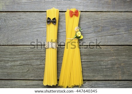 thick thin shape of raw long spaghetti. man woman as bride (with a bouquet of flowers) and groom composition from raw pasta and colorful Farfalle pasta. room for text, stylish pair of illusion