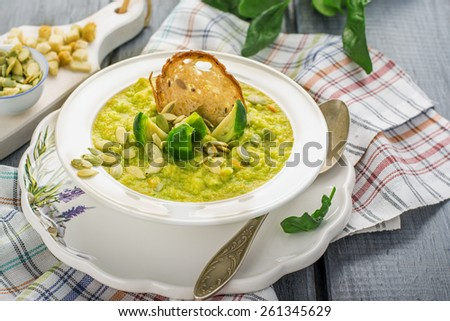 Thick vegetable soup puree with Brussels sprouts, croutons, pumpkin seeds in a white plate on a wooden background with table linens. Selective focus. - stock photo
