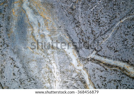 Thick veins of silica in slab of black soapstone. - stock photo