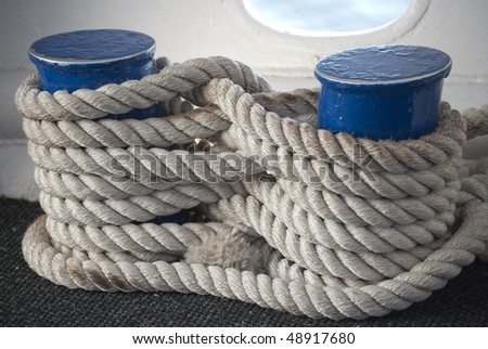 Thick white rope tied in figure eight around piers aboard a ship - stock photo
