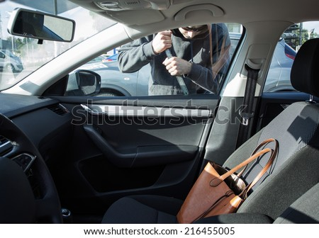 Thief breaking in a car - stock photo