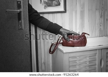 Thief breaking in doors and stealing a handbag. - stock photo