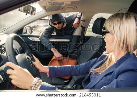 Thief brutally steals woman's handbag while she is driving a car - stock photo