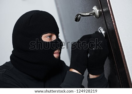 Thief Burglar force lock metal door with a tool during house breaking - stock photo