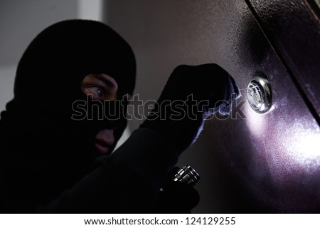 Thief Burglar opening metal door with a crowbar during house breaking - stock photo