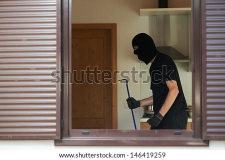 Thief Burglar opening metal door with a crowbar during house breaking - stock photo