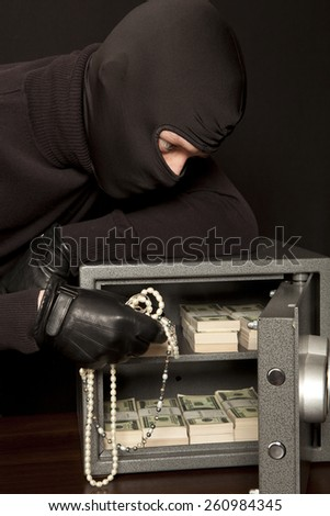 Thief burglar stealing dollar money during home safe code breaking - stock photo