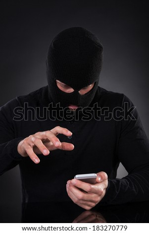 Thief in a balaclava and black outfit standing in the darkness trying to access a stolen mobile phone or a terrorist activating a bomb remotely - stock photo