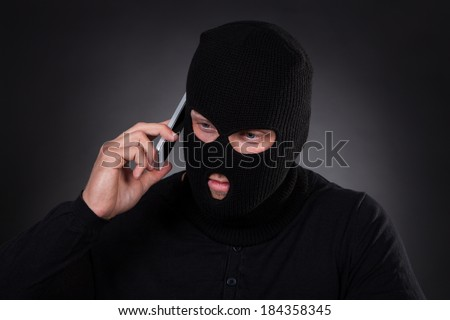 Thief in a balaclava and black outfit standing in the darkness using a stolen mobile phone or a terrorist activating a bomb remotely - stock photo