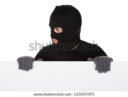 Thief in a balaclava and gloves looking around the edge of a blank sign with copyspace for your text isolated on white