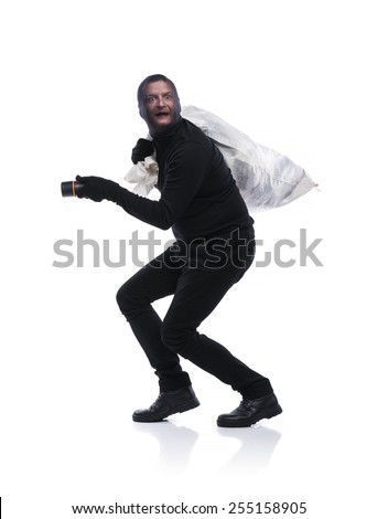 Thief in action carrying a big bag with balaclava on his face, dressed in black. Studio shot on white background. - stock photo