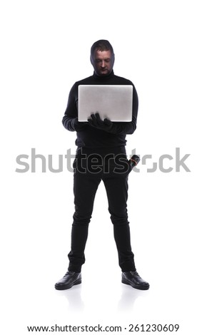 Thief in action stealing information with balaclava on his face, dressed in black. Studio shot on white background. - stock photo