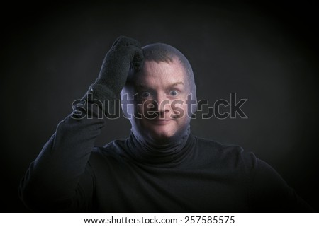 Thief in action with balaclava on his face, dressed in black. Studio shot on black background.