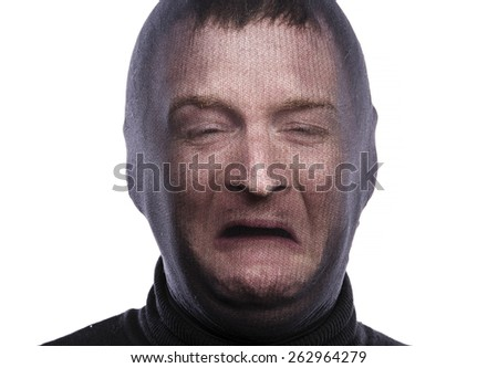 Thief in balaclava making funny faces, dressed in black. Studio shot on white background. - stock photo