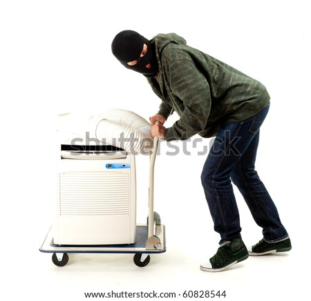 thief in balaclava with mobil air conditioner - stock photo