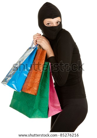 thief in black balaclava with stolen shopping bags - stock photo